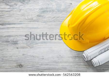 Hard hat construction plans on wooden board building concept.