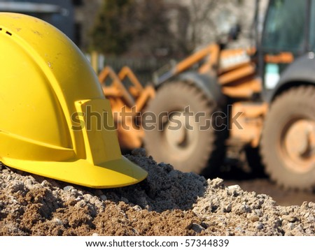 Hard hat on the construction site excavator on the background