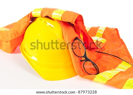 Hard hat, reflective orange vest and safety glasses on white.