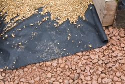 Hard landscaping materials - aggregate, weed membrane and gravel used to lay a garden path, UK