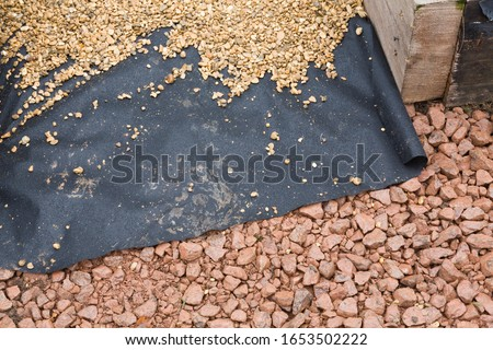 Photo of  Hard landscaping materials - aggregate, weed membrane and gravel used to lay a garden path, UK