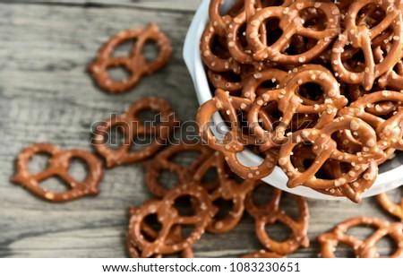 Hard Pretzels or Salted pretzels snack for party in white bowl on wooden floor.