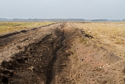 Hard road conditions, motor trail through muddy landscape