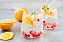 Hard seltzer cocktail with orange, cranberry and mint in glasses and cut oranges on the table. Alcoholic beverage