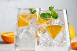 Hard seltzer cocktail with orange, mint and ice.