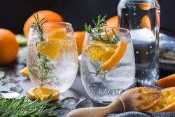 Hard seltzer cocktail with orange, rosemary and bartenders accessories