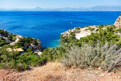 Hard shrub grows on the rocky slopes of the Greek Gulf of Corinth against the backdrop of a blue lagoon on the coast in blur, beautiful top view. Copy space.
