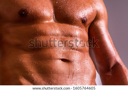 Hard training. Abs. Muscular body in drops of water. Hot workout. Bodybilder with abs