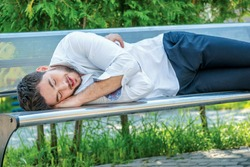 Hard work. A successful businessman in formal clothes sleeping on the street. Young businessman tired from work and lay on the bench