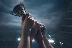 Hard work. Award of victory, male hands tightening the golden cup of winners against cloudy dark sky. Sport, competition, championship, winning, achieving the goal. Prize for success and honor.