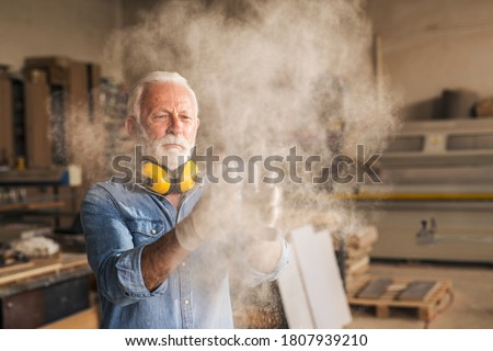Hard working elderly craftsman is at workshop removing sawdust from his work gloves Photo stock ©
