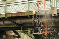 Hard working man is sandblasting the iron bridge. Sandblasting the bridge. Removing rust off the bridge. Preparing the bridge for painting.