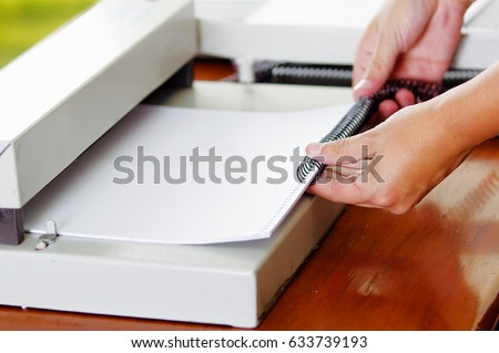 Hard working man using a white useful Binding machine - Shutterstock ID 633739193