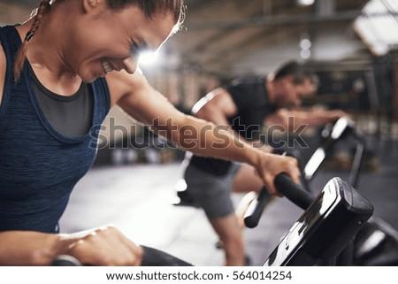Hard working sportive people doing cardio on exercycle. Horizontal indoors shot