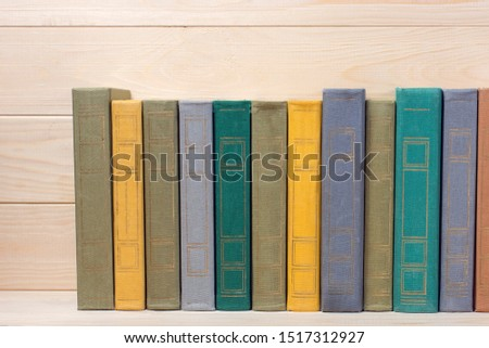 Hardcover books and textbooks on wooden shelf, educational concept