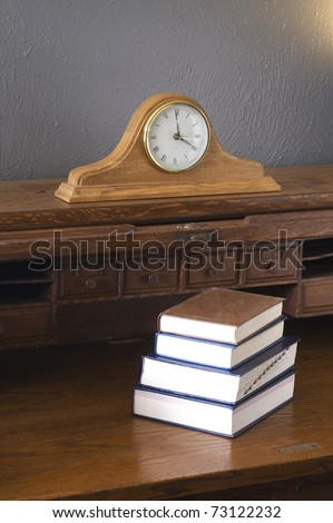 Hardcover Books sit atop on Antique Wood Roll-top Desk with Mantle Clock in Vertical Composition