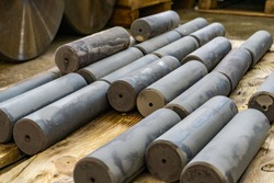 Hardened round blanks for parts after heat treatment lie on a wooden shelf.