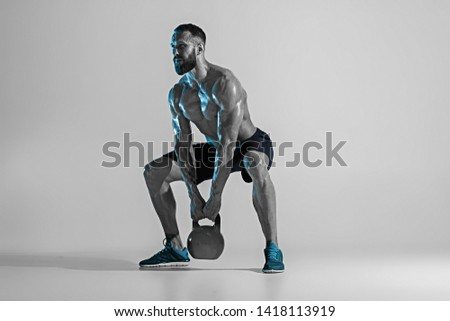 Harder. Young caucasian bodybuilder training over studio background in neon light. Muscular male model with the weight. Concept of sport, bodybuilding, healthy lifestyle, motion and action.