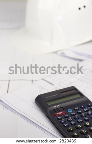Hardhat and calculator lying on construction plans. Focus on the digits of the calculator.