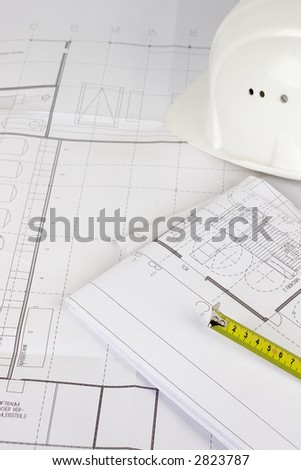 Hardhat and measuring tape lying on construction plans. Focus on the measuring tape. - stock photo