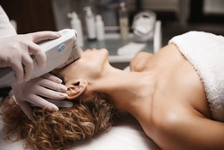 Hardware cosmetology and facelift concept. SMAS face lifting ultrasound procedure carried out in beauty clinic, ultrasonic device rejuvenate women facial skin, enhance collagen production in derma