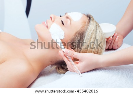 Hardware cosmetology. Closeup picture of lovely young woman with cream mask in a beauty parlour.