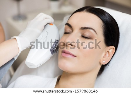 Hardware cosmetology. Skin treatments using photorejuvenation and treatment of benign pigmented lesions. Close-up top-view side-view portrait of a young woman in a cosmetology clinic.