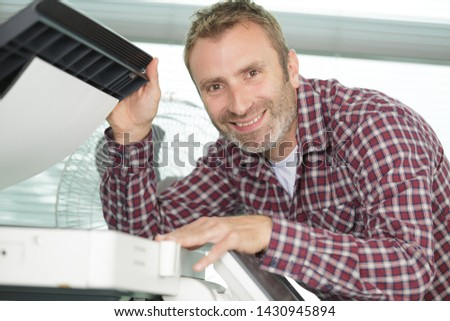 hardware repairman repairing broken printer fax machine #1430945894