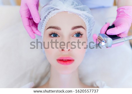 Hardware skin care. A young girl cares for her face. Beauty treatment. Procedures. Advertising.