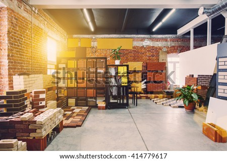 Hardware store office. Samples colored bricks. Brick wall interior. Sunlight from big window