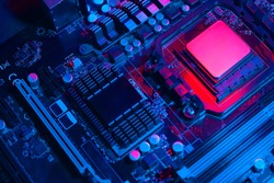 Hardware technology concept in neon light. Motherboard in blue-red light. Computer  component. Dark photo.
