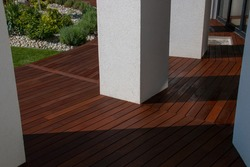Hardwood Ipe decking, a freshly painted and stained wood deck on the exterior patio of the modern house design