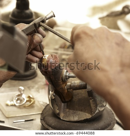 hardworking Goldsmith working on an unfinished 22 carat gold ring with his aged hands