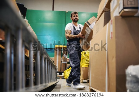 Hardworking tattooed bearded manual worker walking trough warehouse and carrying very heavy big box ready for export.