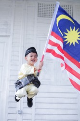 Hari Merdeka Malaysia National Day declared on 31 August every year annually. Boy jump and running happily on green grass field holding Malaysian flag namely Jalur Gemilang