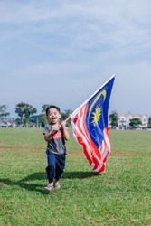 Hari Merdeka Malaysia National Day declared on 31 August every year annually. Boy running happily on green grass field holding Malaysian flag namely Jalur Gemilang