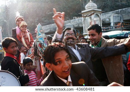 HARIDWAR, INDIA - JANUARY 14: The groom goes to bride, friends are dancing in front of the horse, to delay the moment of betrothal in traditional Indian wedding, January 14, 2009 in Haridwar, India. - stock photo