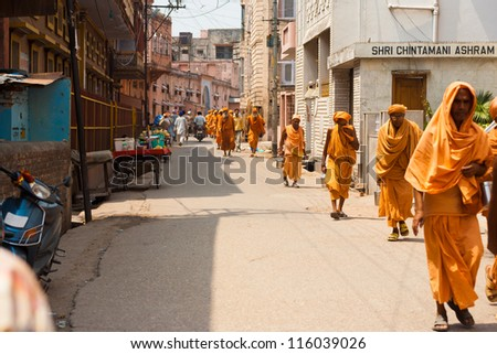 Haridwar, India - May 21, 2009: Many religious men wearing orange robes walking down a street during a pilgrimage to the holy city of Haridwar