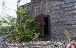 Harjumaa/Estonia-04.15.2020: Old smoker built into the forest. Meat smoker fire place metal door. Opened metal door in a outdoor fireplace. Fish smoker near the seaside. Juminda peninsula forest