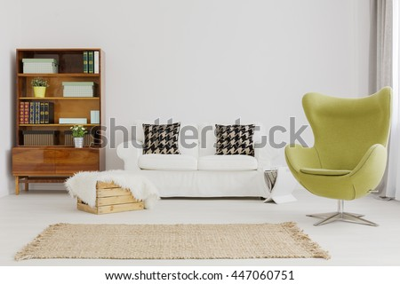 Harmonious and elegant living room decor, with a renovated modernist bookcase and a green egg chair