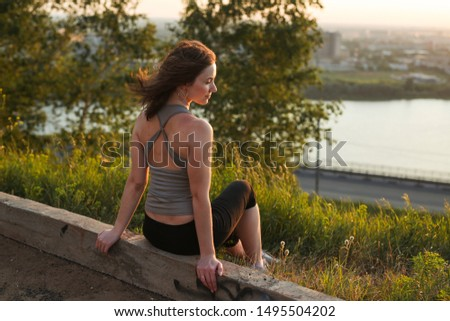 harmonious calm Young pretty Caucasian woman in a sports T-shirt sitting in a park over a river at sunset, the concept of sport and harmony in the city