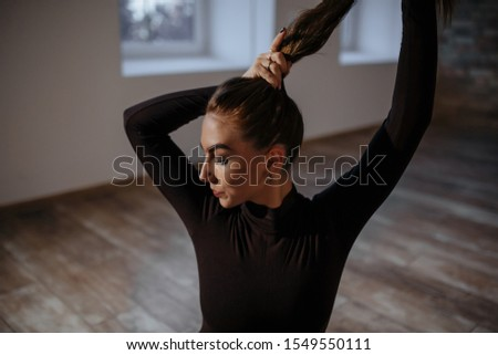 harmonous young beautiful girl with long black hair in a long-sleeve bodysuit stands near the wall in the room makes sensual poses, poses with her face and hands at dusk in the dark with backlight