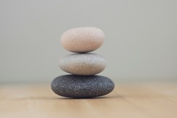 Harmony and balance, cairns, simple poise pebbles on wooden light white gray background, simplicity rock zen sculpture in daylight
