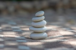 Harmony and balance cairns, simple poise stones on white and brown textile checkered background, rock zen sculpture in sunlight, five white pebbles, single tower and simplicity