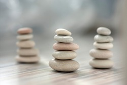 Harmony and balance, three cairns, simple poise pebbles on wooden light white gray background, simplicity rock zen sculpture, river stones in towers