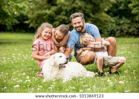 Harmony and luck in the family concept with parents and kids and dog in the park