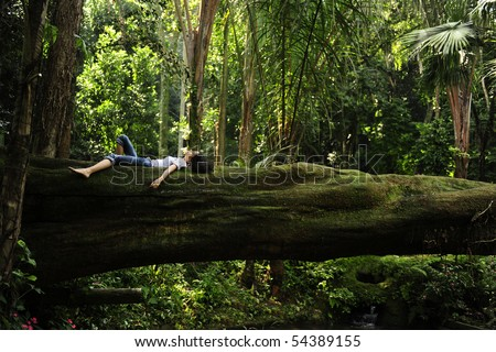 harmony in nature: woman relaxing on a fallen tree trunk in a tropical forest - stock photo