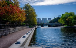 Harmony of Nature and Civilization. Tranquil Autumn Landscape with Footpath and Pond at Lechmere Canal Park in Boston.