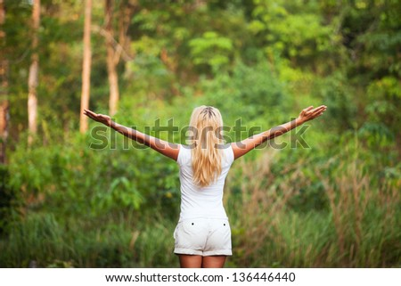 harmony with nature, back woman with raised hands in the forest