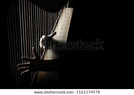 Harp player. Hands playing Irish harp strings. Music instrument closeup. Harpist with celtic harp #1161574978